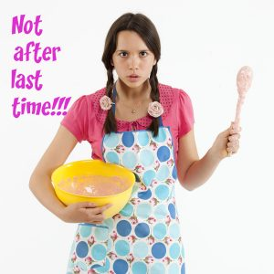 An angry teenage girl dressed for baking waves her wooden spoon like a weapon.