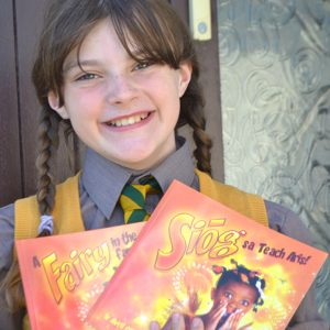 A girl in school shirt and tie holds her dual language English and Irish book