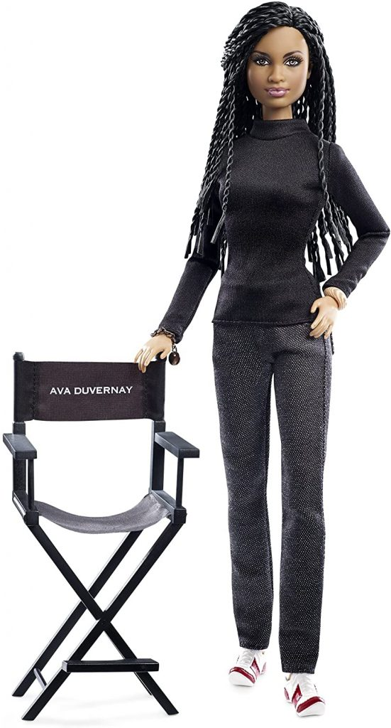 black Barbie doll standing next to a director's chair