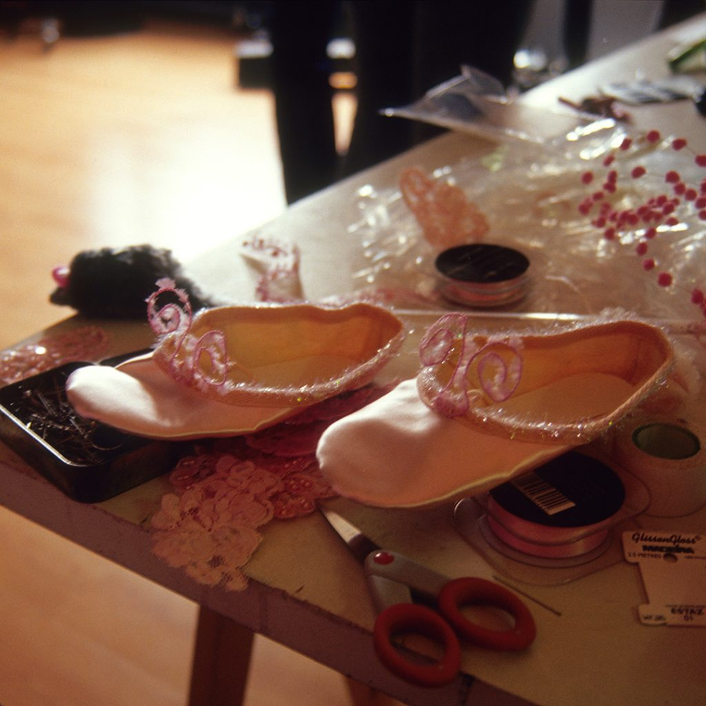 a table with ballet shoes and seamstress's equipment