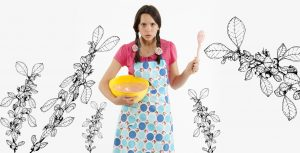 Angry girl in rose patterned apron waving a wooden spoon