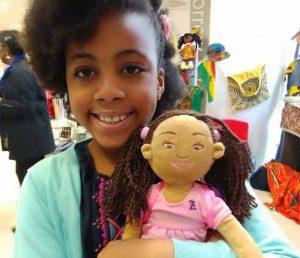 smiling little black girl holding a black plush doll