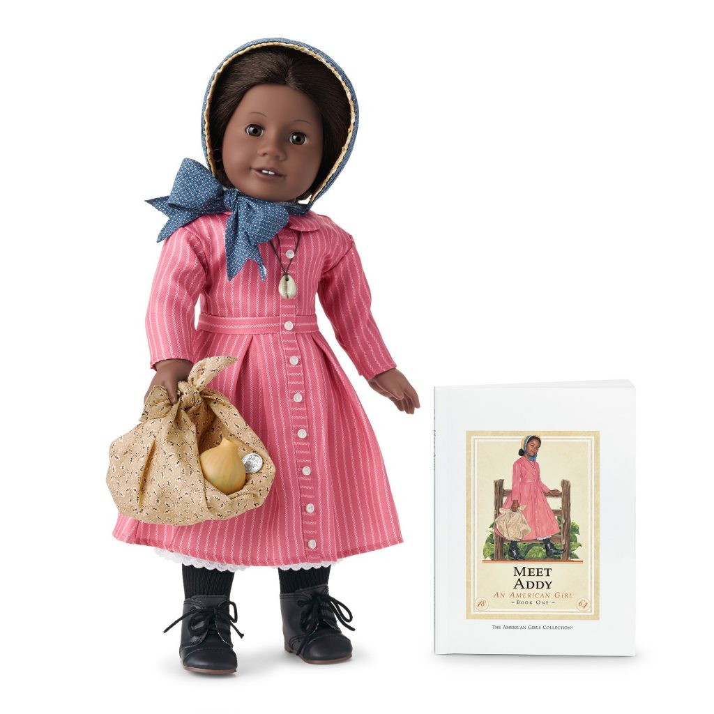 Smling black doll in historic costume next to her storybook