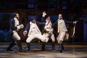 Four actors in historical costume dancing onstage in the musical Hamilton