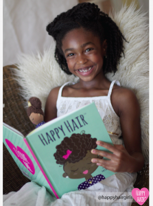 Smiling young black girl reading a book
