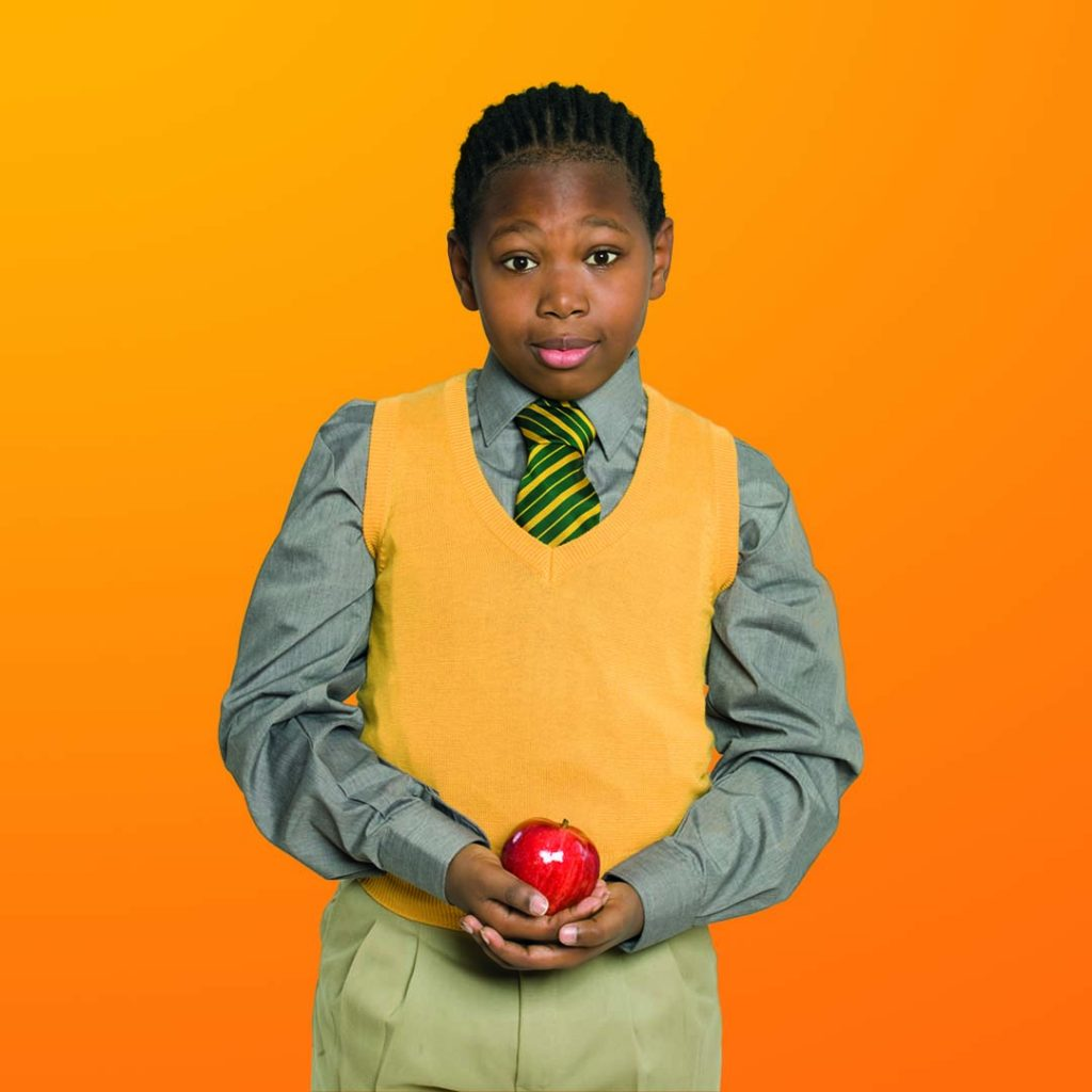 Sam in school uniform with apple for teacher