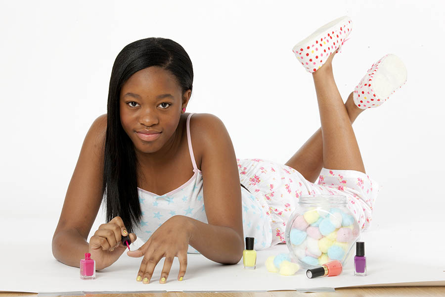 Smiling girl in pyjamas painting her nails.