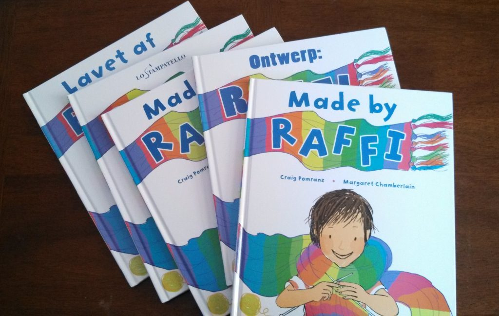 "A stack of copies of the book ""Made by Raffi"" in different languages"