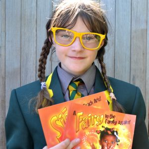 A girl in a school blazer with shirt and tie holds her dual language English and Irish book