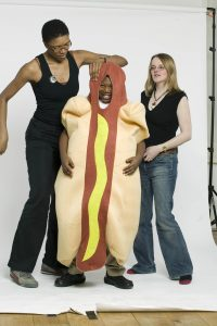 A boy in a hot dog costume is helped by two women