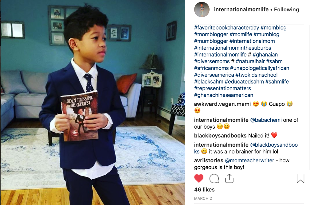 A boy dressed as the book character Jaden Toussaint holds a copy of the Jaden Toussaint book by author Marti Dumas.