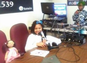 A little girl DJ sits next to her Zolie Zoi doll while preparing to read a story on air.