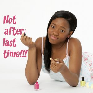 A teenage girl in pyjamas has a bemused expression. She is painting her nails in different colours.