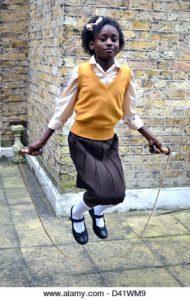 Little black girl in school uniform skipping beside a brick wall
