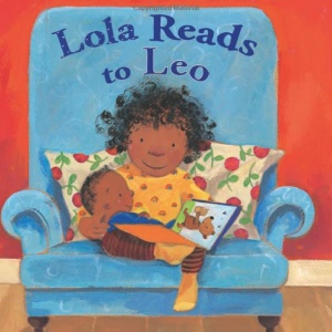 a little girl with an afro hairstyle reads to her baby brother who is on her lap