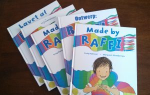"""A stack of copies of the book """"Made by Raffi"""" in different languages"""