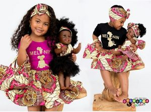 Two girls in Africa prints hold dolls also in African prints