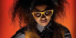 Scowling schoolgirl in yellow glasses with Albert Einstein hair-do
